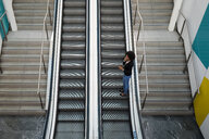 Businesswoman on the phone standing on escalator - MAUF02012
