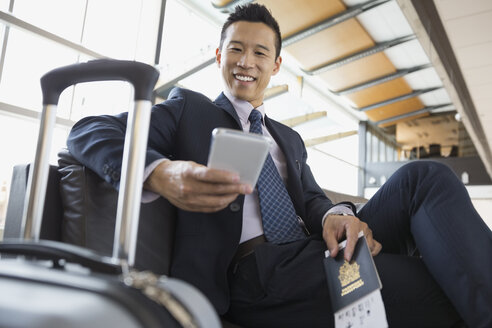 Businessman with cell phone waiting in airport - HEROF01927