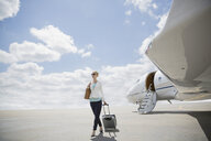 Businesswoman pulling suitcase on tarmac near corporate jet - HEROF01957