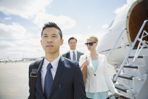 Business people on tarmac with corporate jet - HEROF01960