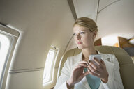 Businesswoman text messaging on corporate jet - HEROF01972
