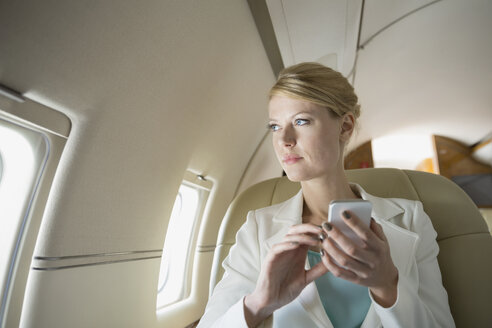 Businesswoman text messaging on corporate jet - HEROF01972