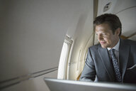 Businessman with laptop looking out corporate jet window - HEROF01975