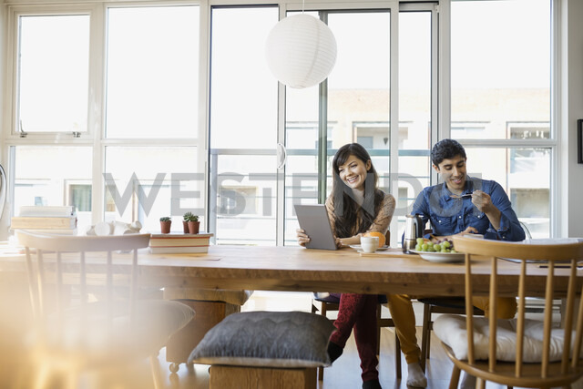 Couple using digital tablet and eating at table - HEROF02005 - Hero Images/Westend61