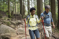 Couple hiking with poles on trail in woods - HEROF02020