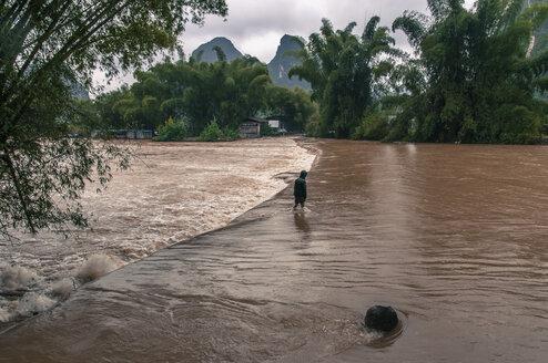 Man crossing flooded road, Yangshuo, Guangxi Province, China - AURF07942
