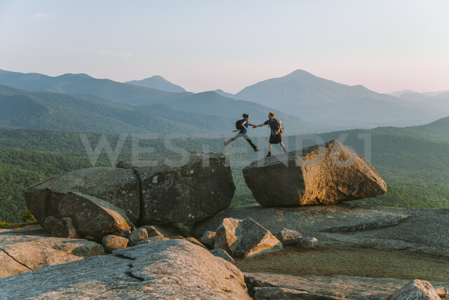 Man helping woman jump across boulder, Pitchoff Mountain, Adirondack Mountains, New York State, USA - AURF07948 - Cavan Images/Westend61