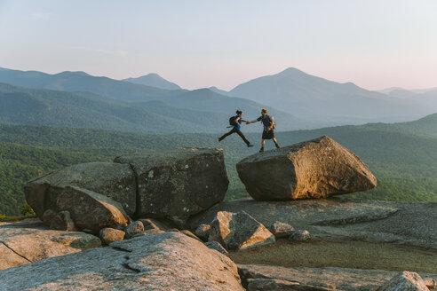 Man helping woman jump across boulder, PitchoffMountain, Adirondack Mountains, New York State, USA - AURF07948