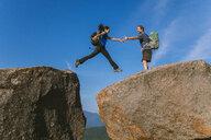 Man helping woman jump across boulder, PitchoffMountain, Adirondack Mountains, New York State, USA - AURF07954
