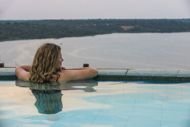 Africa, Uganda, Queen Elizabeth National Park, Woman relaxing in a pool above Kazinga channel - RUNF00508