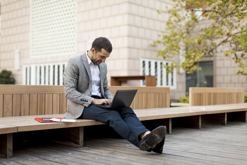 Smiling businessman sitting on a bench using laptop - MAUF02023