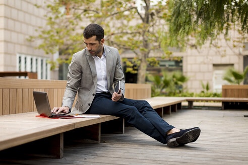 Businessman sitting on a bench using laptop - MAUF02026