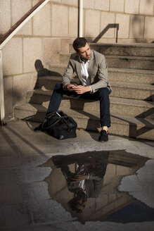 Businessman with bag sitting on stairs using cell phone - MAUF02035