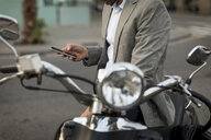 Close-up of businessman on motorscooter checking cell phone - MAUF02041