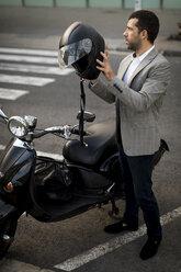 Businessman next to motorscooter putting on helmet - MAUF02044
