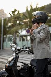 Businessman next to motorscooter putting on helmet - MAUF02047