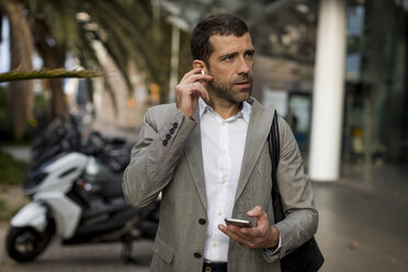 Businessman with cell phone in the city applying earbuds - MAUF02050