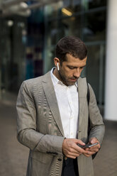 Businessman with cell phone and bluetooth earbuds in the city - MAUF02053