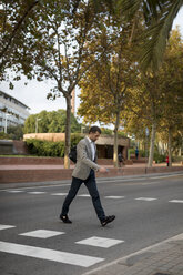Businessman with bag crossing a street in the city - MAUF02062