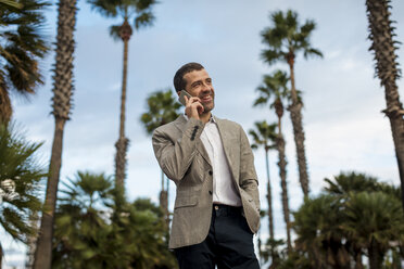 Happy businessman talking on cell phone with  palm trees in background - MAUF02065