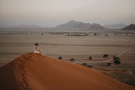 Namibia, Namib desert, Namib-Naukluft National Park, Sossusvlei, woman sitting on Elim Dune at sunset - LHPF00235