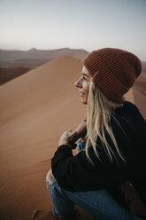 Namibia, Namib desert, Namib-Naukluft National Park, Sossusvlei, smiling woman sitting on Dune 45 at sunrise - LHPF00238