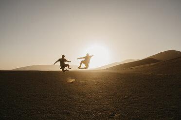 Namibia, Namib desert, Namib-Naukluft National Park, Sossusvlei, two men jumping at Dune 45 at sunrise - LHPF00244