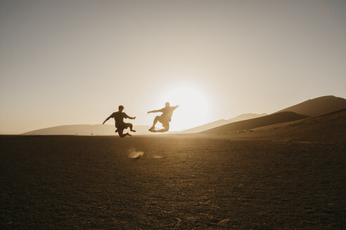 Namibia, Namib desert, Namib-Naukluft National Park, Sossusvlei, two men jumping at Dune 45 at sunrise - LHPF00244