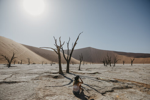 Namibia, Namib desert, Namib-Naukluft National Park, Sossusvlei, woman sitting in Deadvlei - LHPF00250