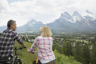 Couple standing with mountain bikes on hillside - HEROF02055