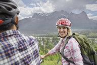 Couple riding mountain bikes on hillside - HEROF02067