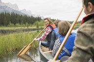 Family rowing canoe in still lake - HEROF02091
