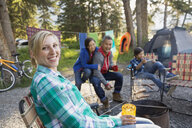 Family relaxing together around campfire - HEROF02109