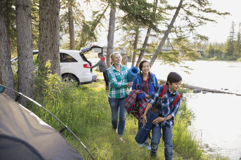 Family carrying gear at campsite - HEROF02142