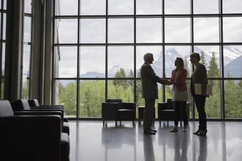 Business people shaking hands in office lobby - HEROF02232