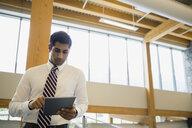 Businessman using digital tablet in office lobby - HEROF02253