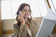 Businesswoman talking on cell phone in office lobby - HEROF02256