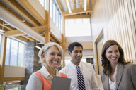 Business people smiling in office lobby - HEROF02259