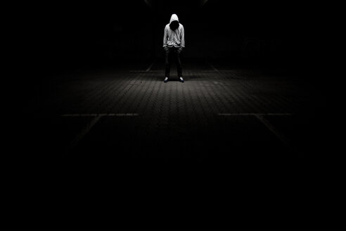 Hooded man looking down surrounded by darkness - INGF11390
