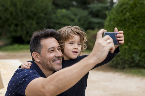 Happy father and son on taking a selfie in park - MAUF02071