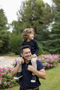 Happy father carrying son on shoulders in park - MAUF02077
