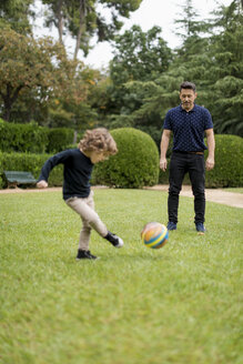 Father and son playing football in park - MAUF02080