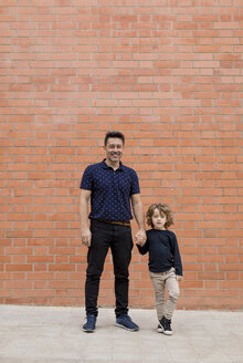 Portrait of father and son standing hand in hand at brick wall - MAUF02089