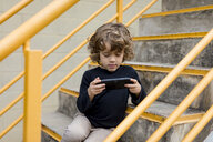 Boy sitting on stairs playing with handheld game console - MAUF02101