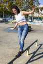 Young woman with earbuds balancing on rail in the city - MGIF00260