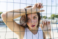 Portrait of young woman behind fence - MGIF00284