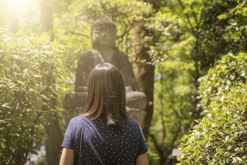 Woman looking at Buddha statue at a sunny day - EPF00512