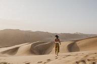 Namibia, Namib, back view of woman walking barefoot on desert dune - LHPF00264