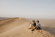 Namibia, Namib, two friends sitting on desert dune looking at view - LHPF00270