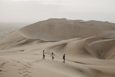 Namibia, Namib, three friends walking down desert dune - LHPF00276
